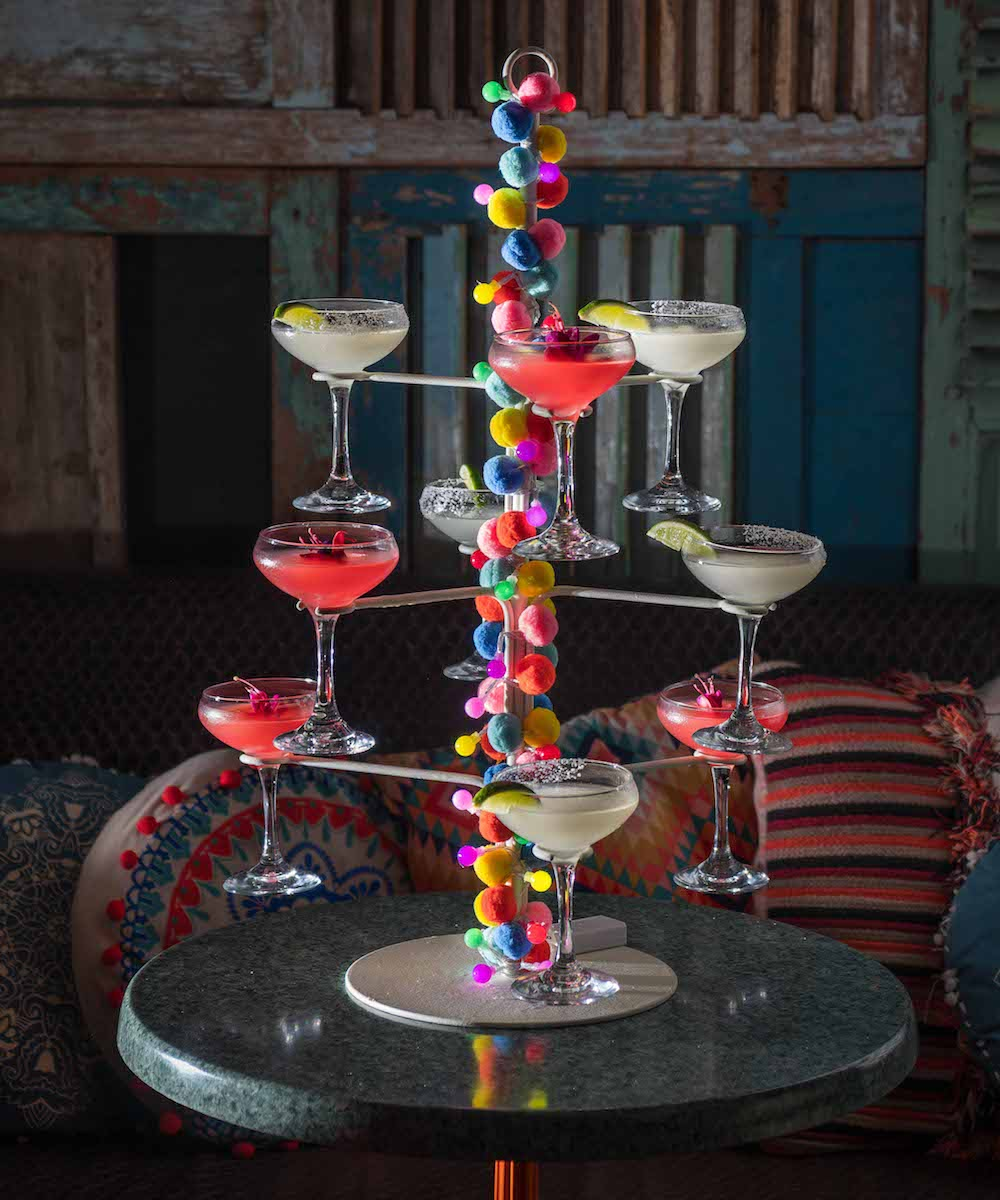 A tower filled with classic and watermelon frozen margaritas, decorated with bright pom-poms