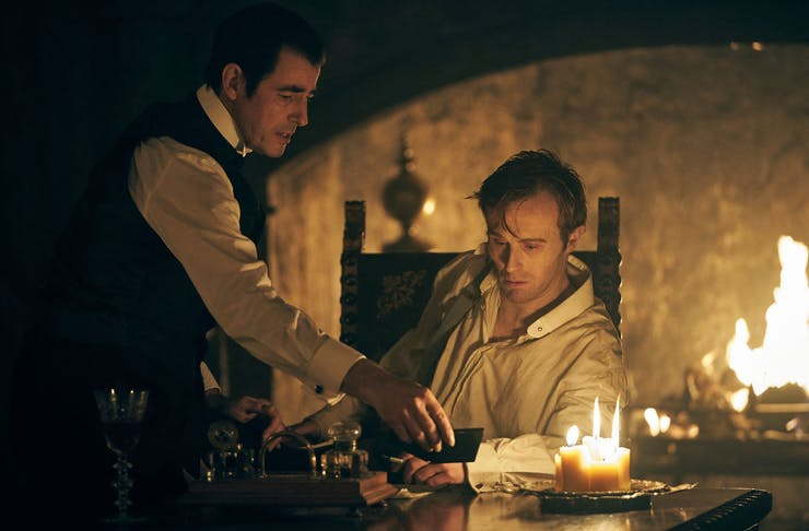 A dark still from the Netflix Series Dracula of a man sitting at a table and a man standing, with a roaring fire behind them.