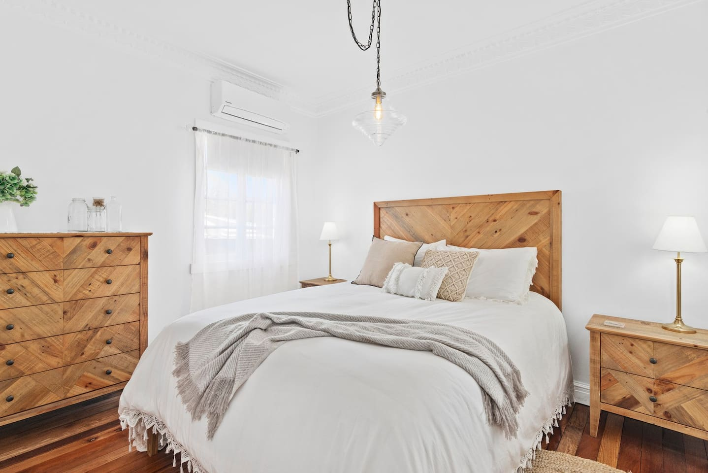 a stylish white bedroom with a beautifully made bed