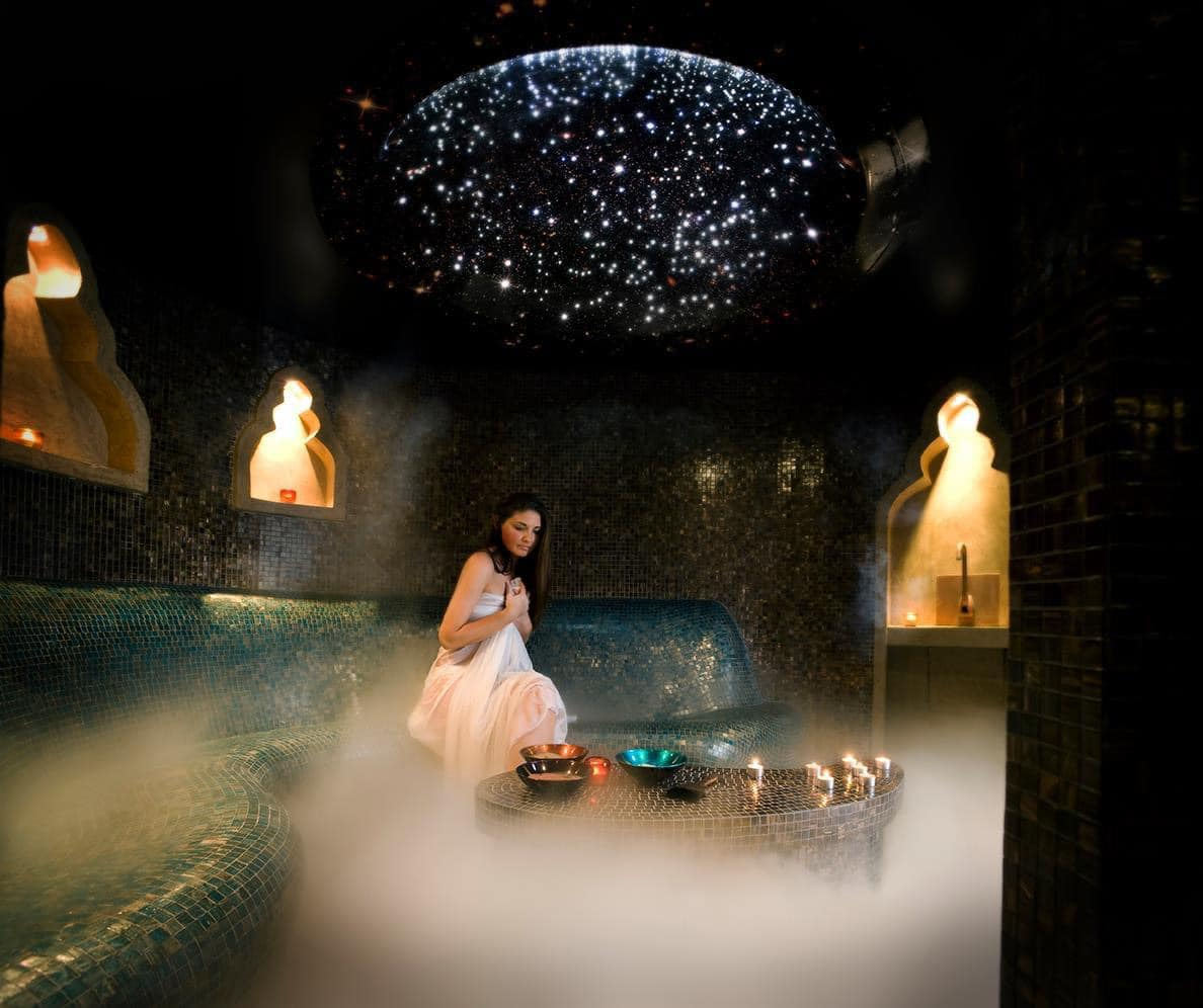 a woman in a tiled steam room