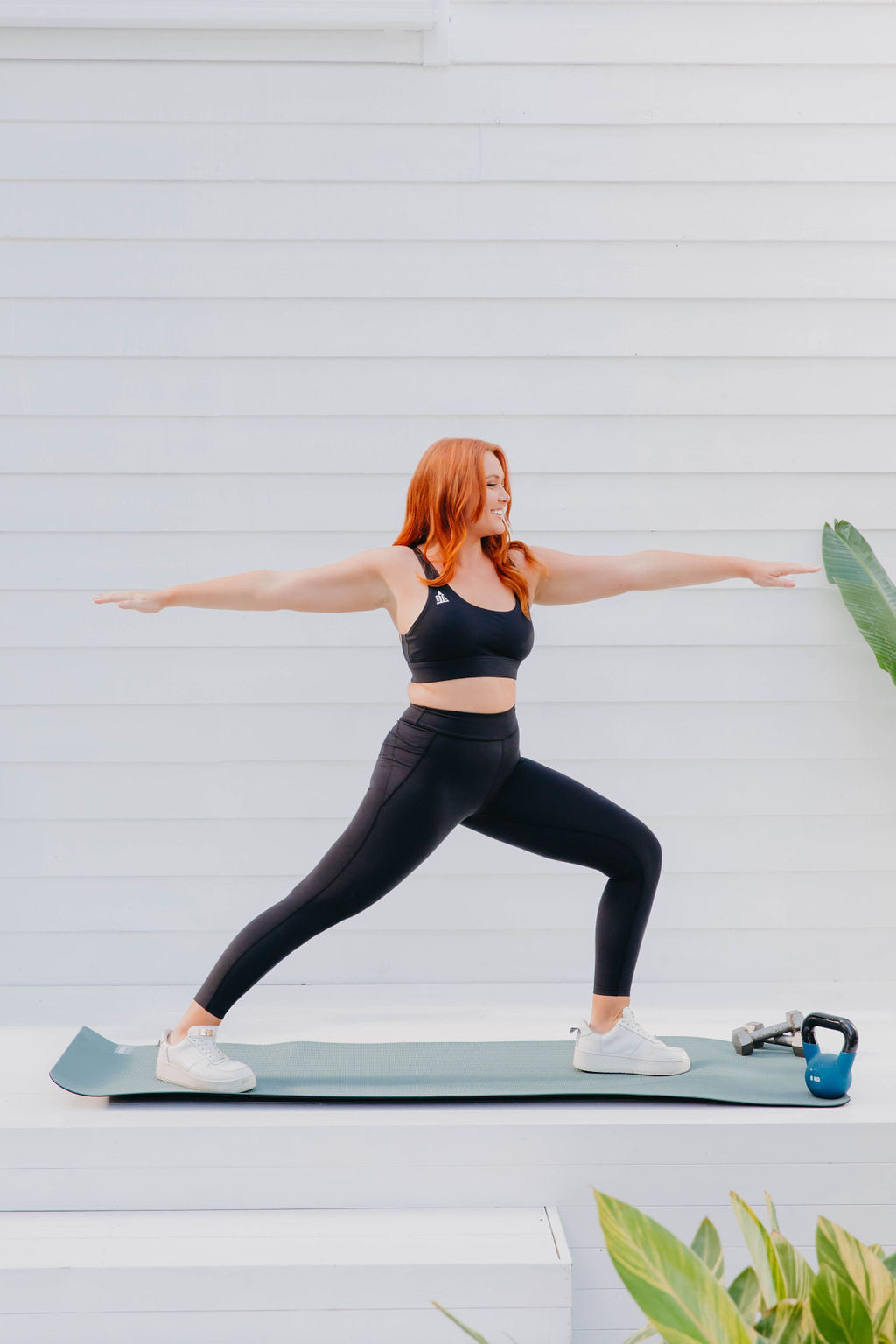 a woman in black activewear doing pilates