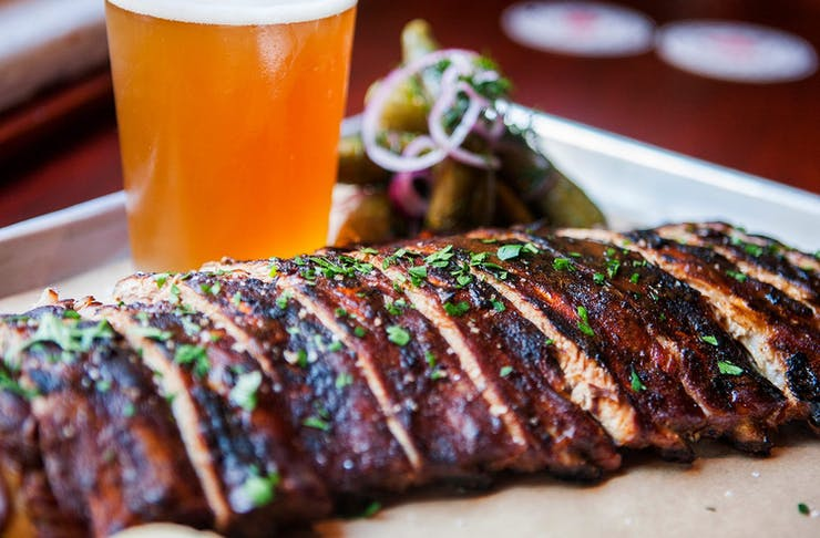 A plate of ribs served with a beer.