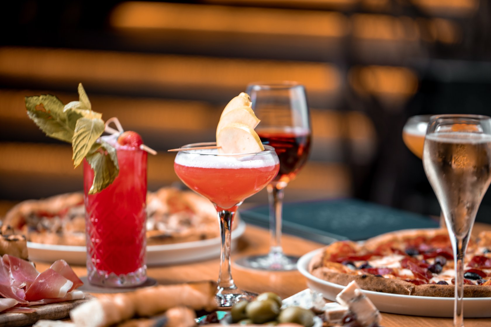 several cocktails on a table with plates of Italian food
