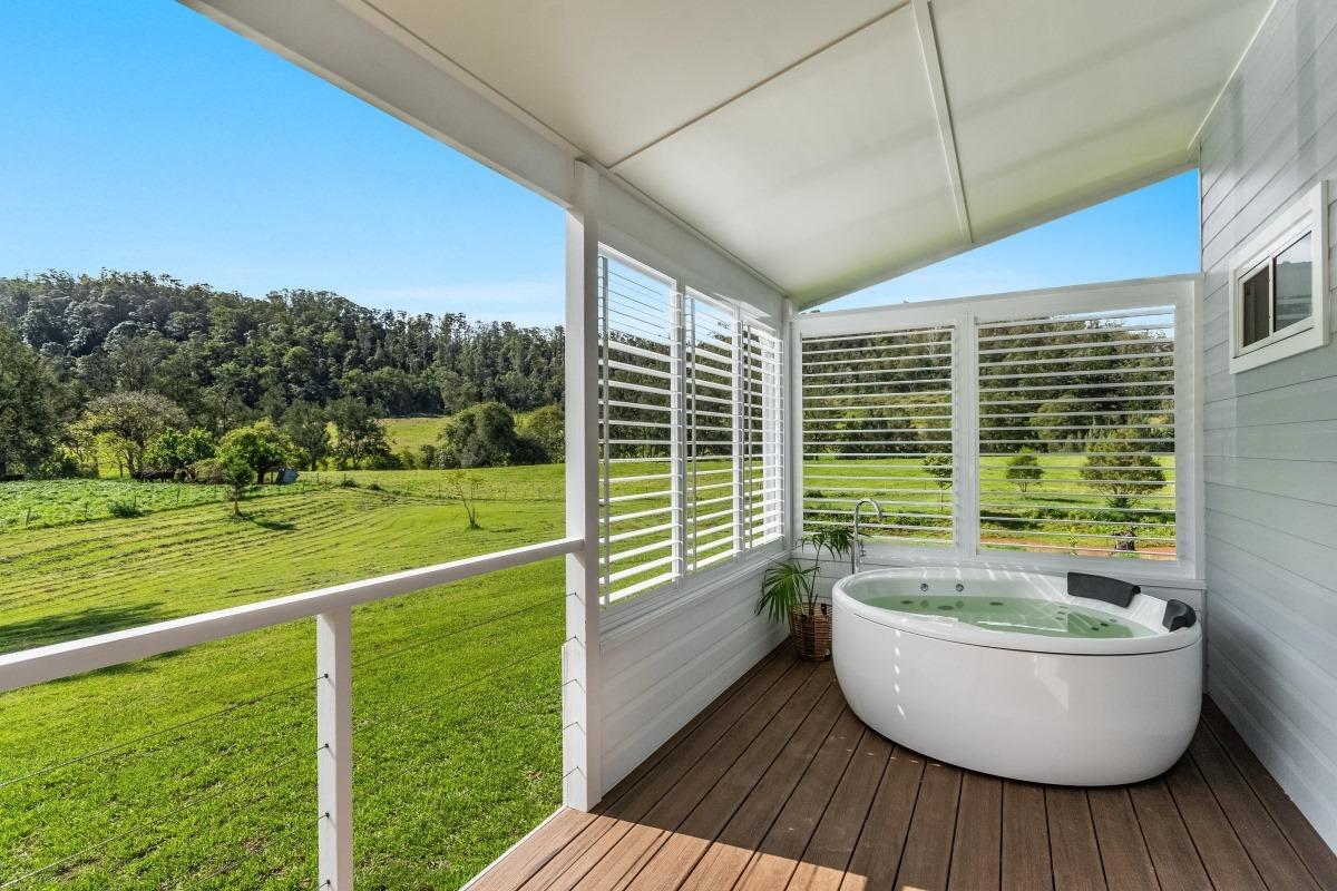a large bath outside on a small verandah overlooking green hills