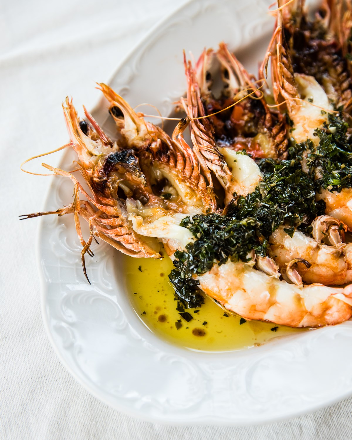a plate of grilled prawns drizzled in oil