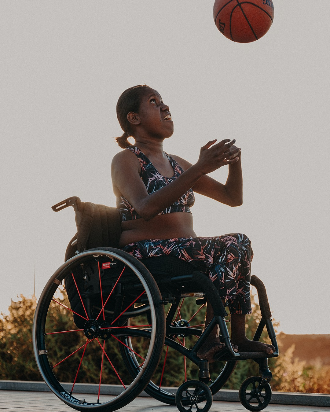 a woman in a wheelchair in activewear throwing a basketball