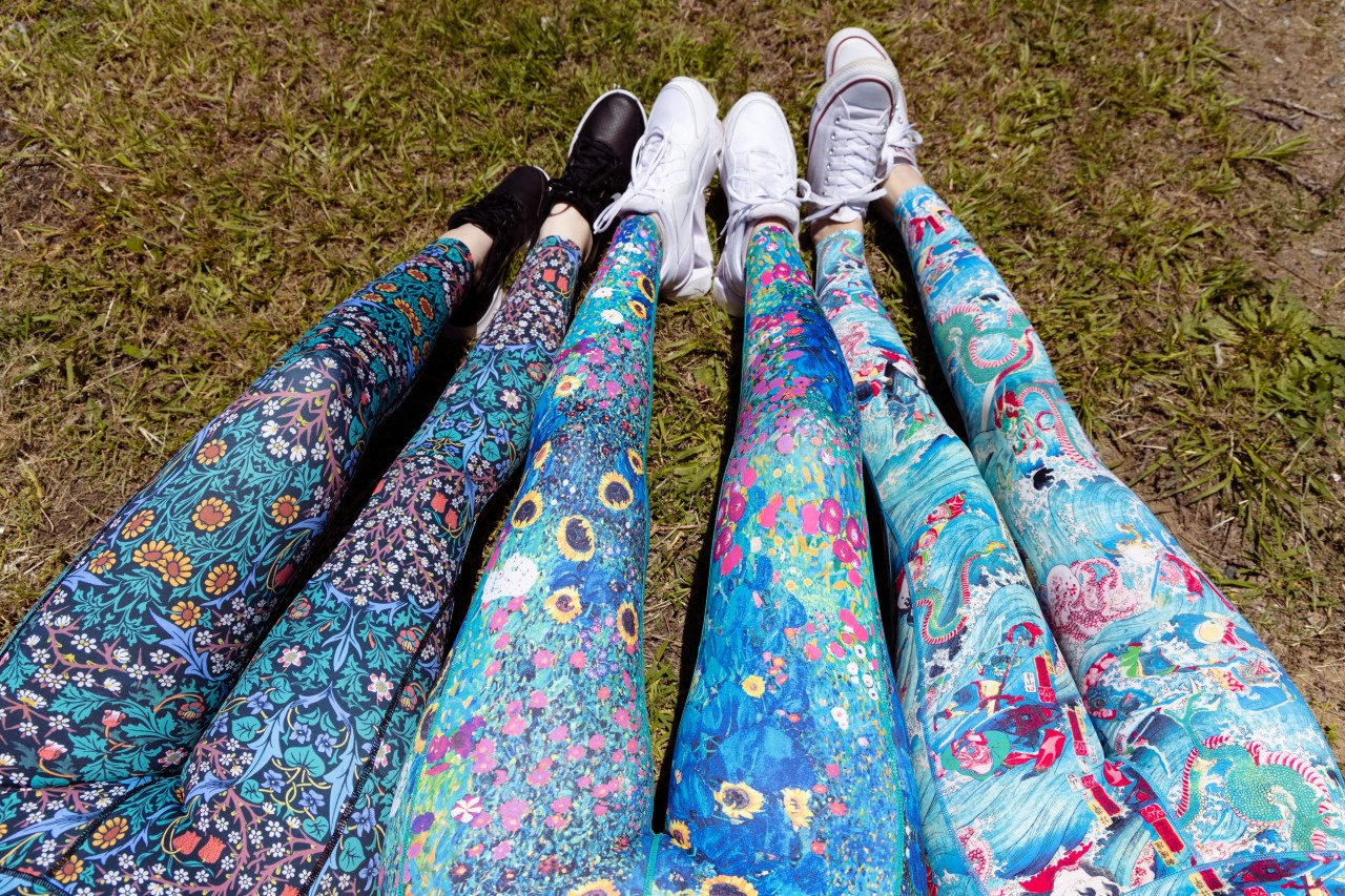 three sets of legs on grass wearing colourful tights