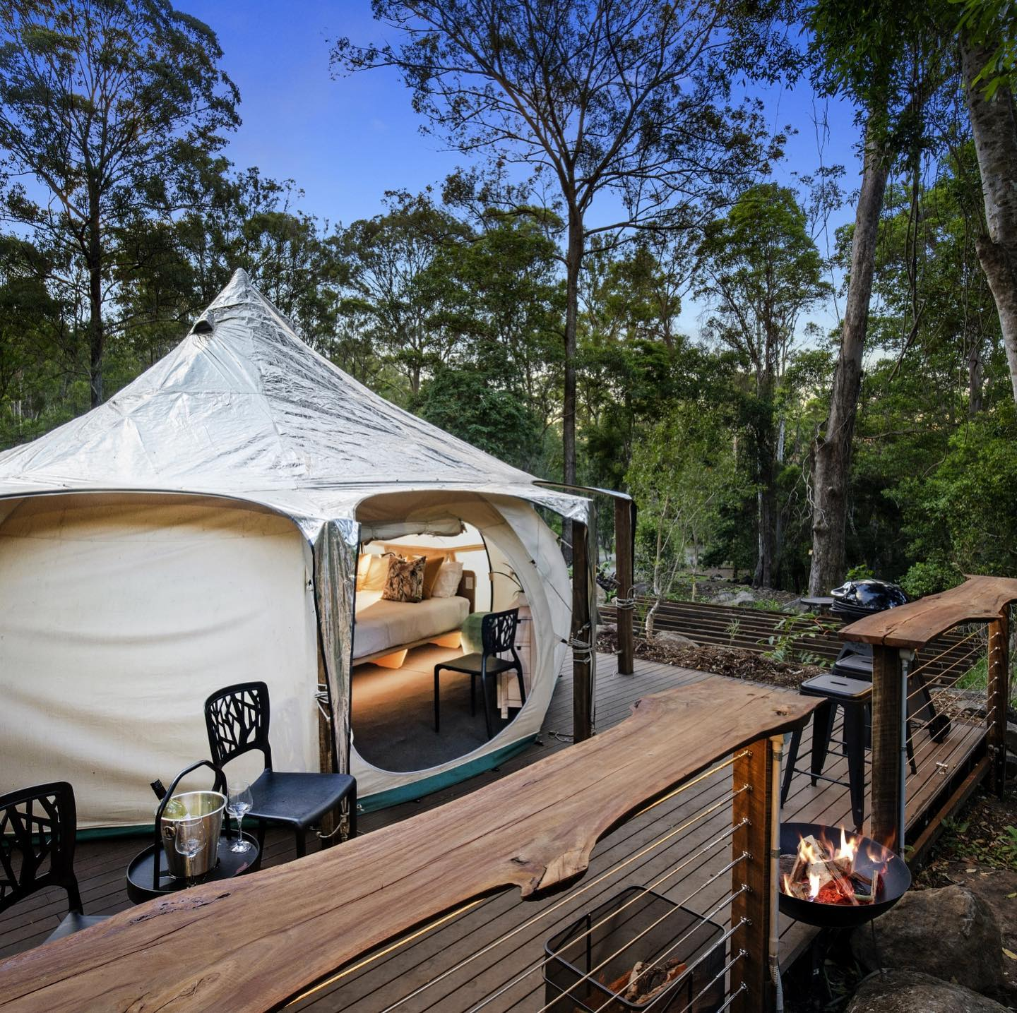 a lotus-shaped tent on a deck in the forest