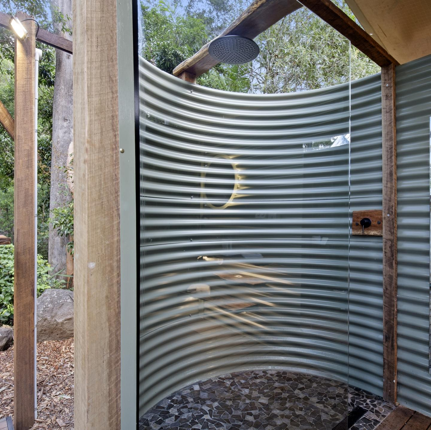 a shower enclosed by corrugated iron with an open roof