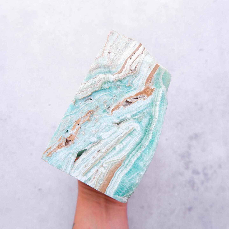 a hand holding slab of aqua crystal