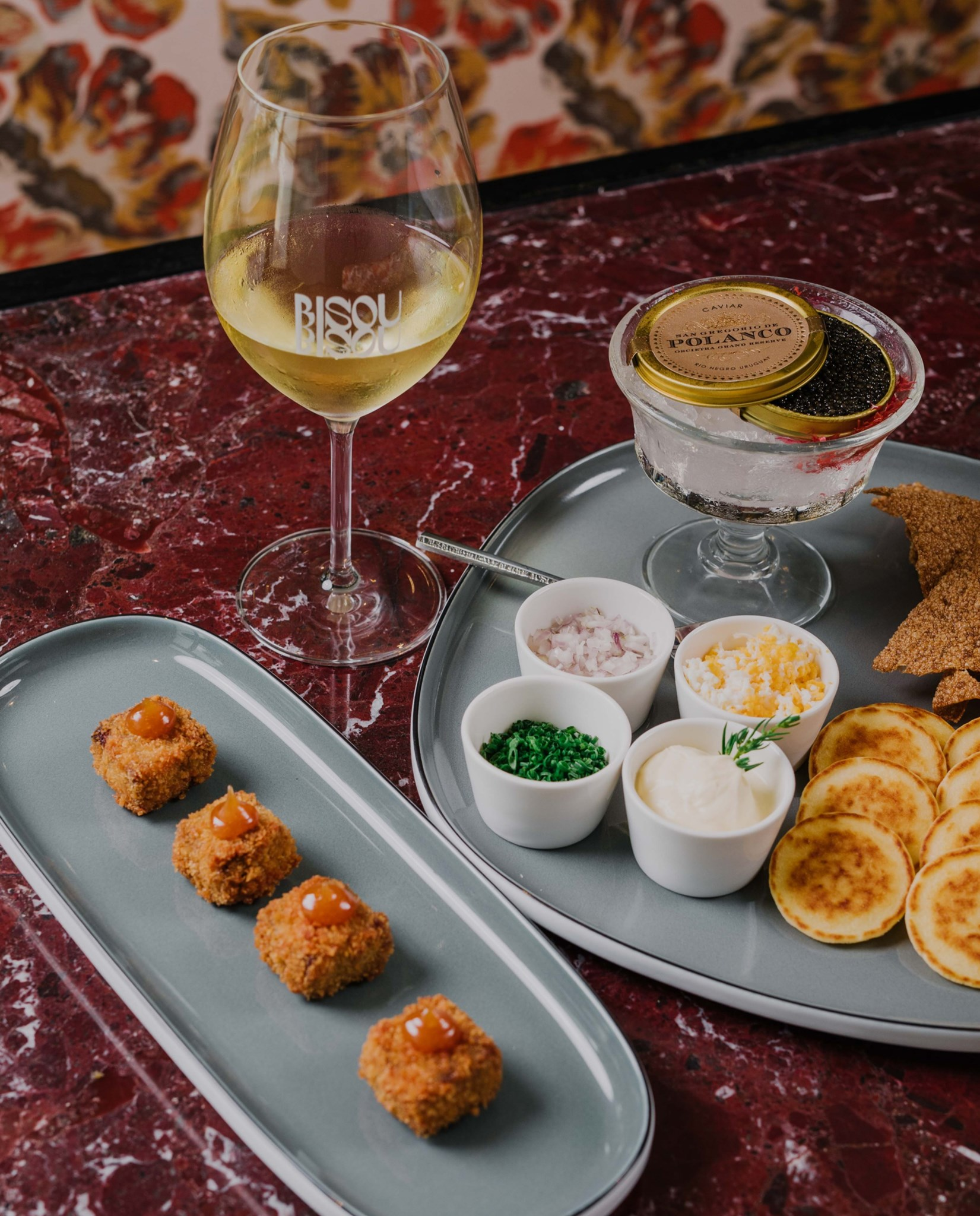 a plate of caviar and blinis with a glass of wine