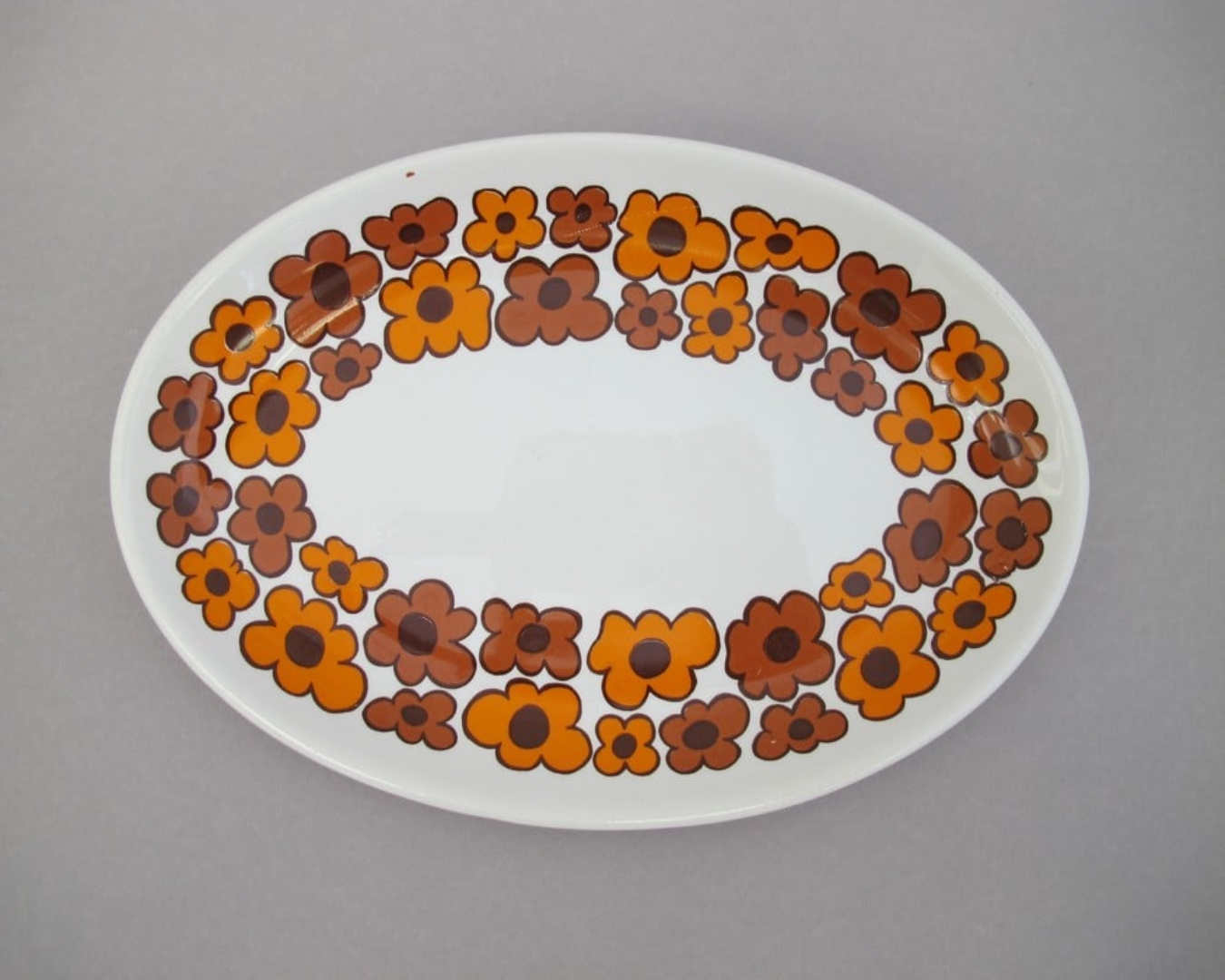 A ceramic plate decorated with joyful orange and dusky red flowers.