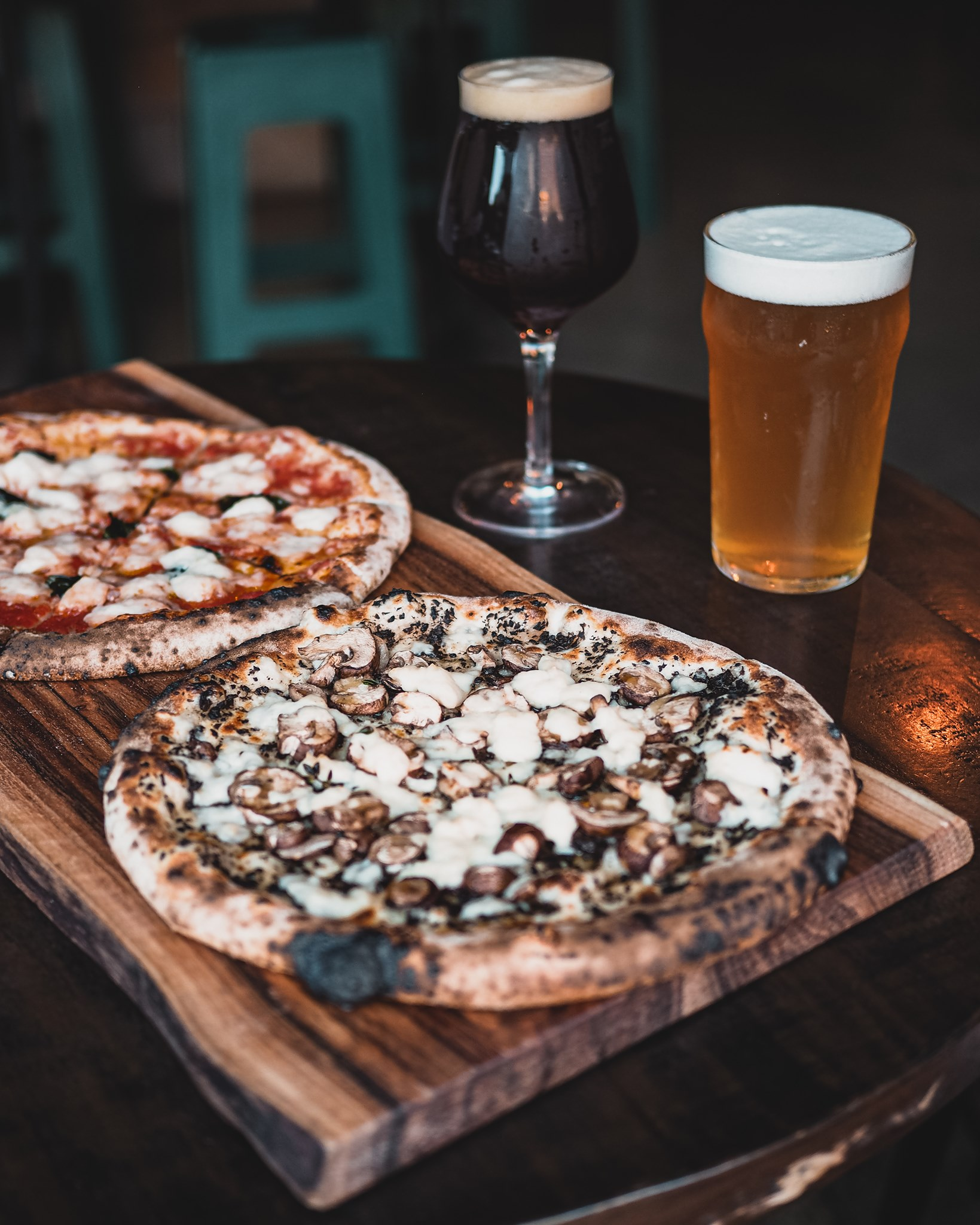 two vegan pizzas on a table with two beers