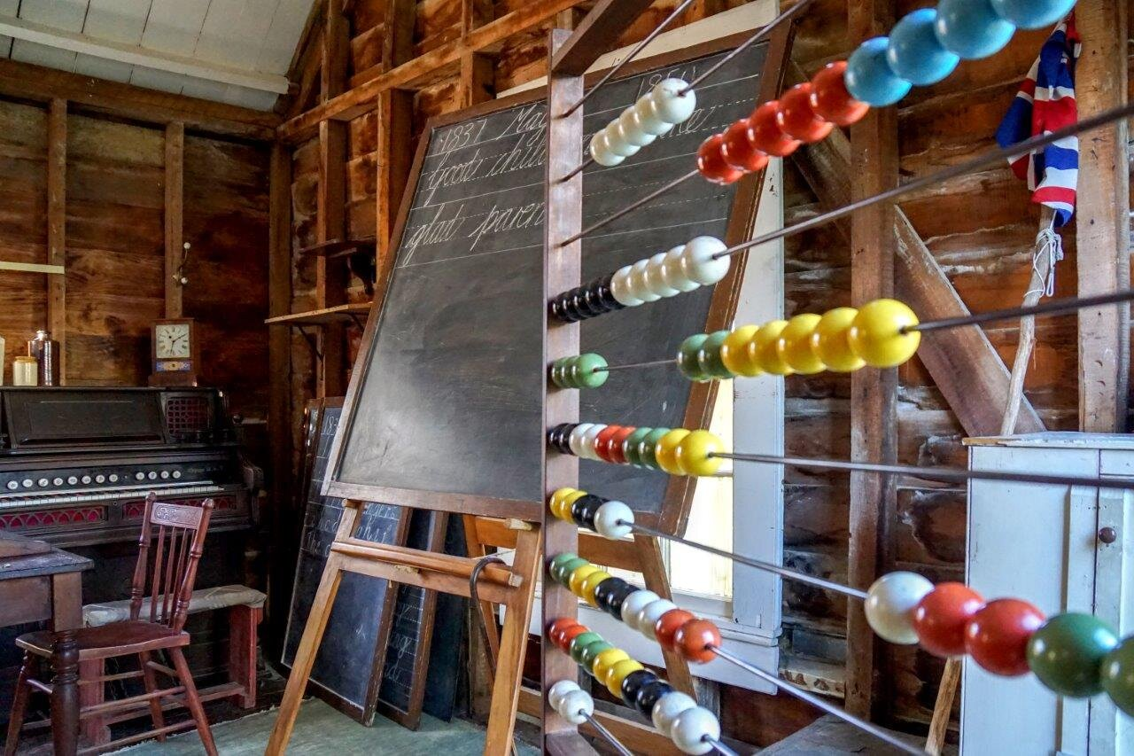 A wooden school house from the 1980s: in the foreground is an abacus with brightly coloured beads, a blackboard with cursive handwriting sits in the mid-ground and at the bag of the room is an organ.