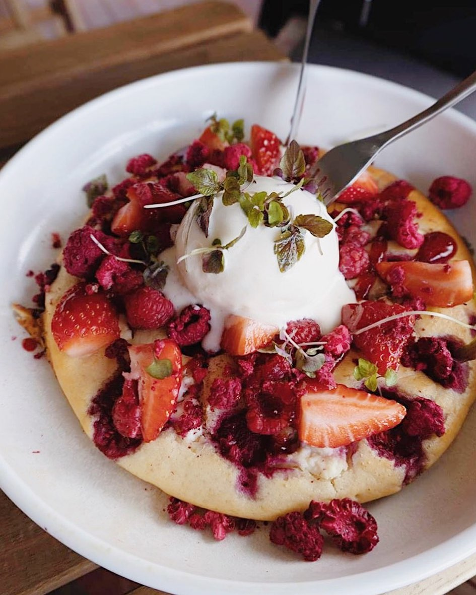 a plate of hotcakes topped with berries