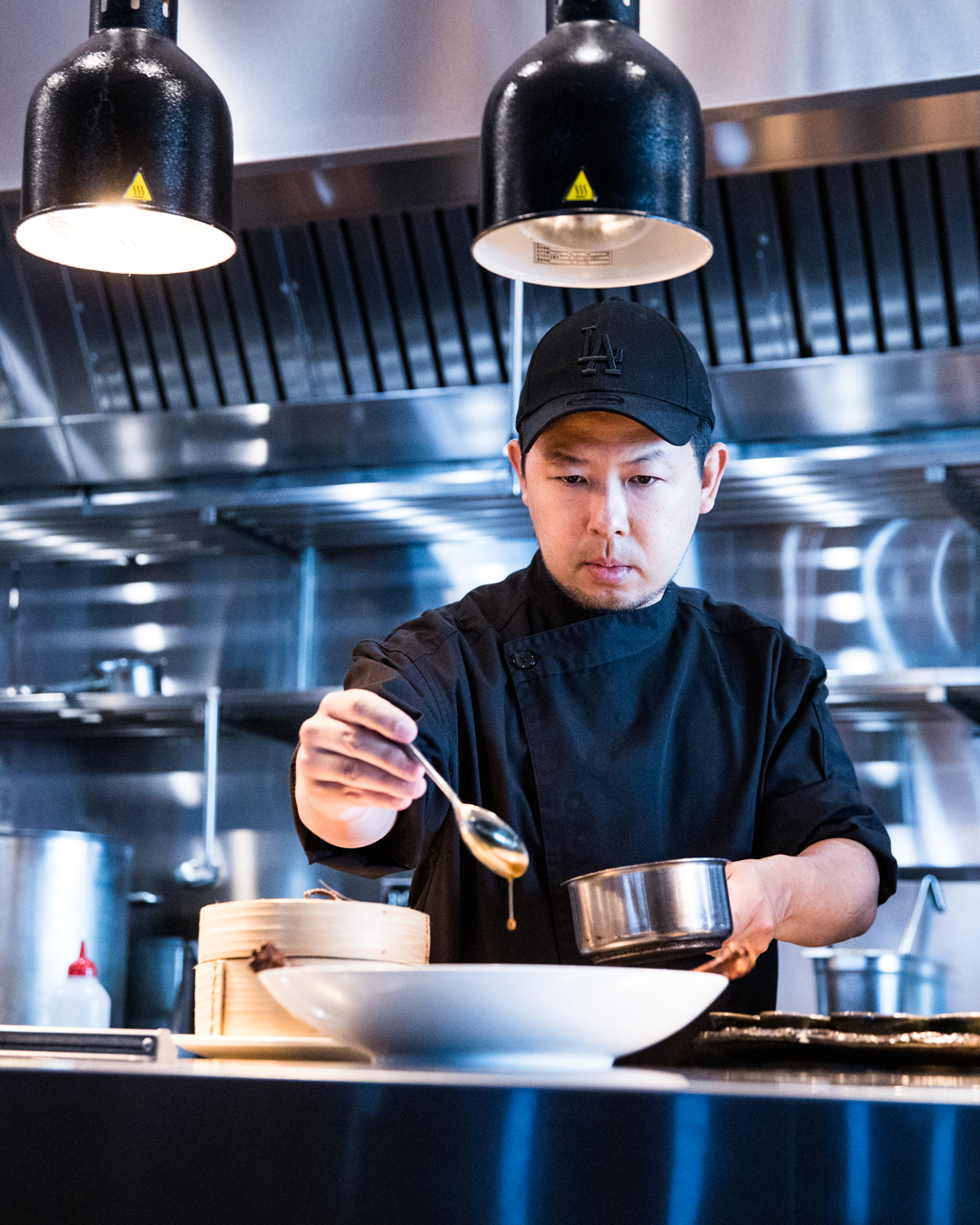 Chef Chase Kojima wearing a cap standing at the pass in his restaurant serving a dish.