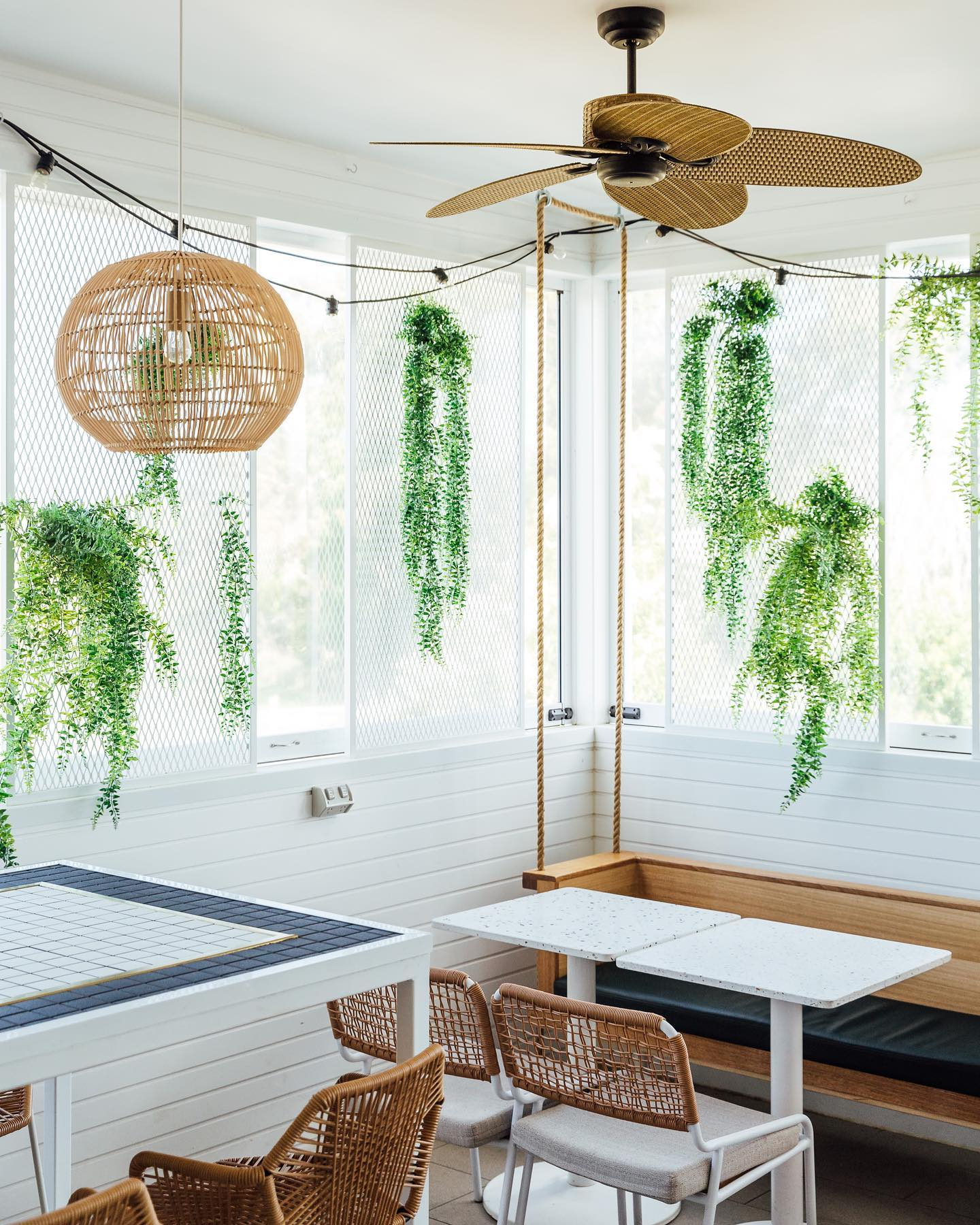 a corner of a cafe with hanging greenery