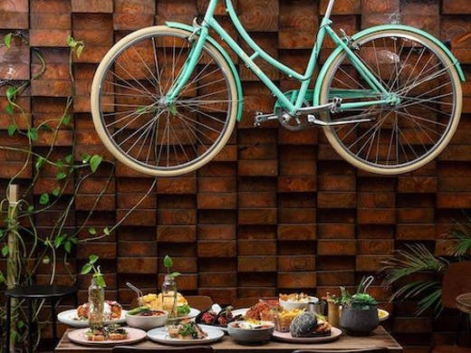 Image of blue bicycle hanging up at 1982 Food + Coffee