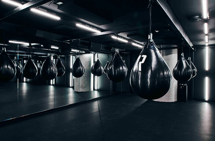 Black boxing bags hanging in a neon-lit gym.