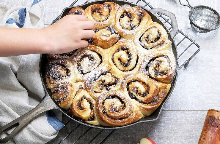 A cast iron pan with yummy cinnamon scrolls with a hand reaching out to pinch some.