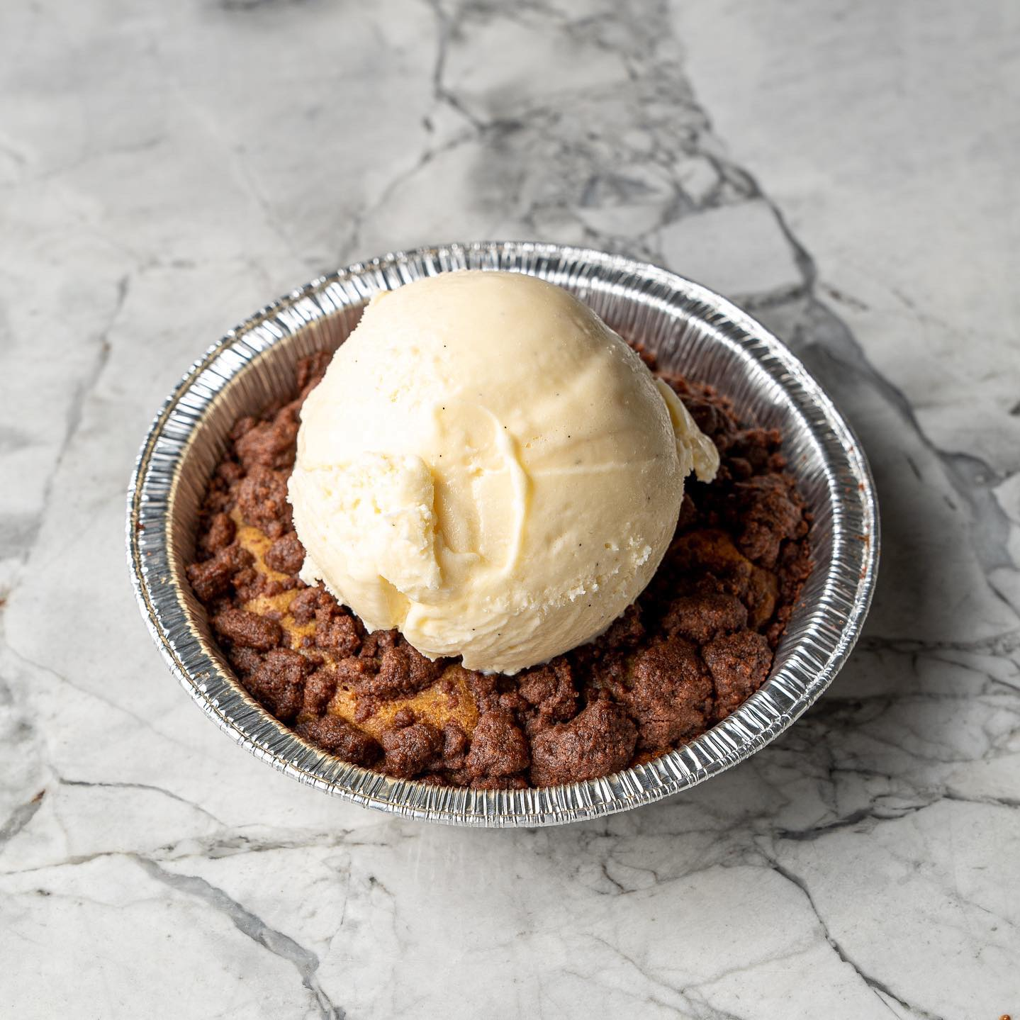 a single serve cookie pie with a scoop of gelato on top