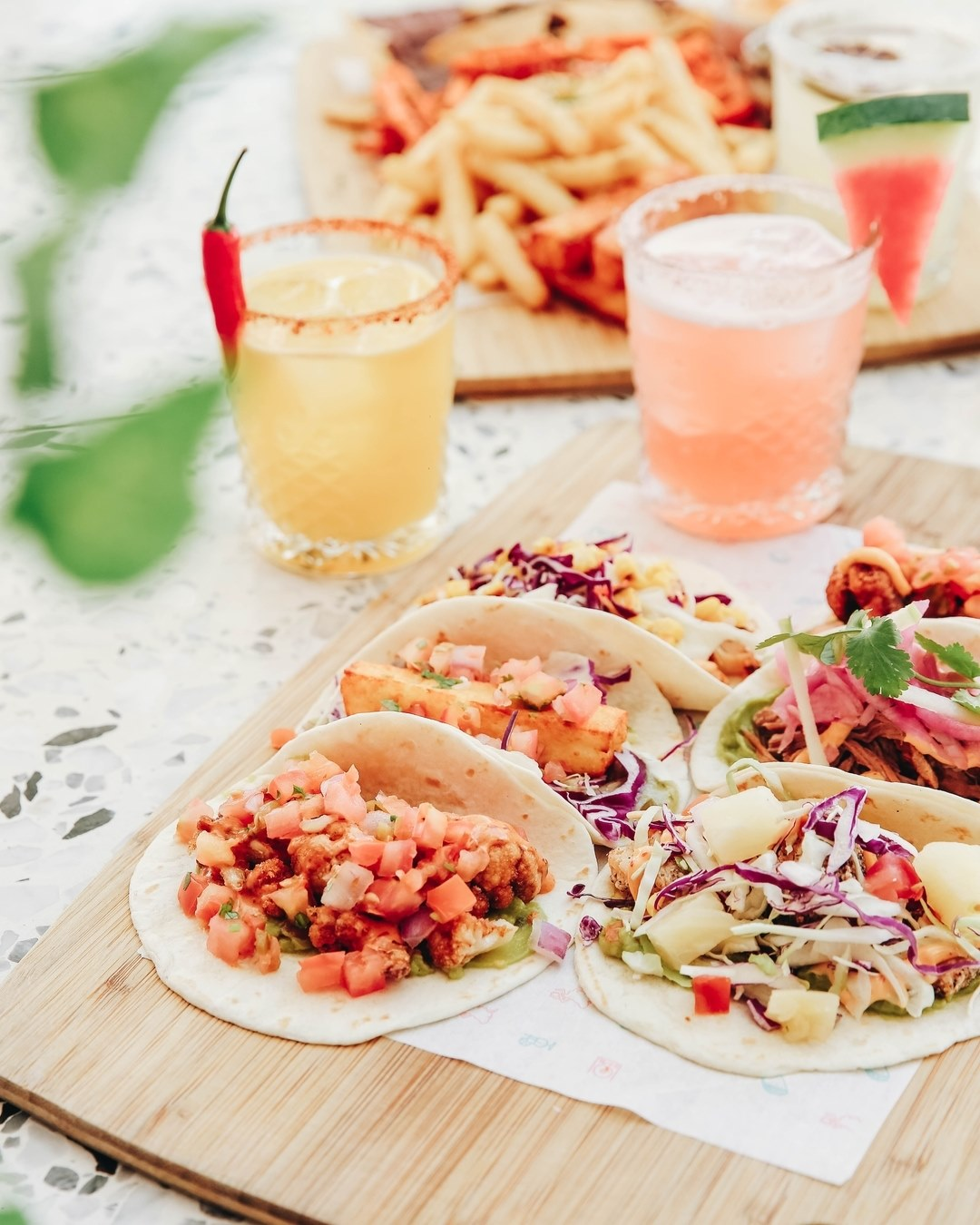 a plate of tacos and a cocktail