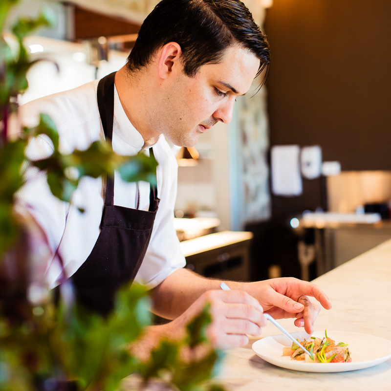 Chef plating up a gourmet dish at the pass