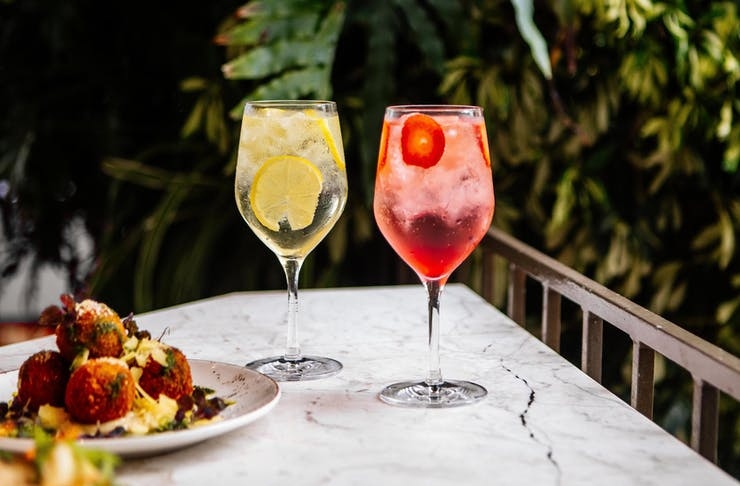 Two tall crisp cocktails sit next to a plate of food.