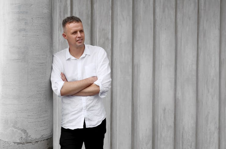A man stands in front of a grey wall wearing a white shirt and black pants, with his arms crossed.
