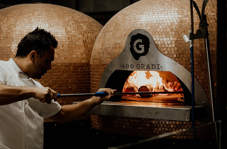 Johnny Di Francesco putting a pizza into a wood-fired oven.