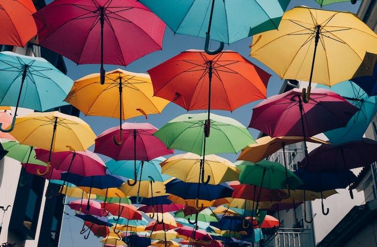 Rainbow umbrellas hanging in a city alleyway.