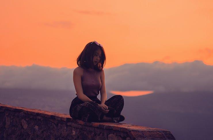 Women meditating outdoors at sunset
