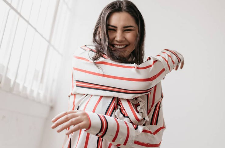Girl in a red and white-striped blouse looking and smiling at the camera.