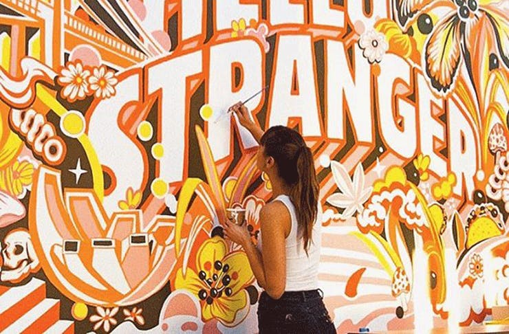 Gemma O'Brien paints a brightly coloured orange mural that reads 'Hey Stranger'.