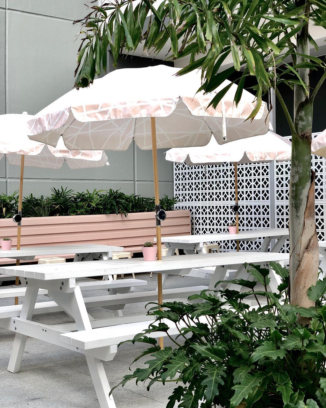 white picnic tables under pink striped umbrellas in a courtyard