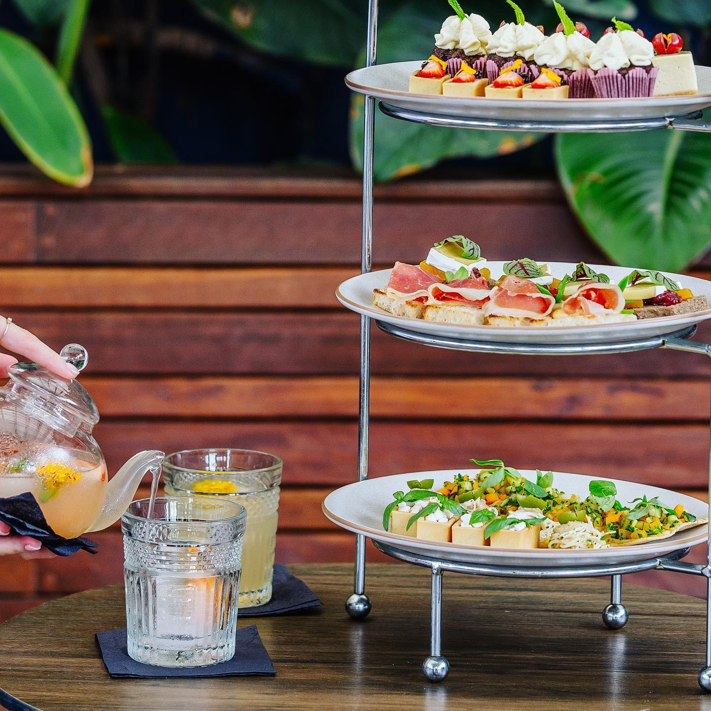 a high tea tower and a cocktail being poured from a glass teapot