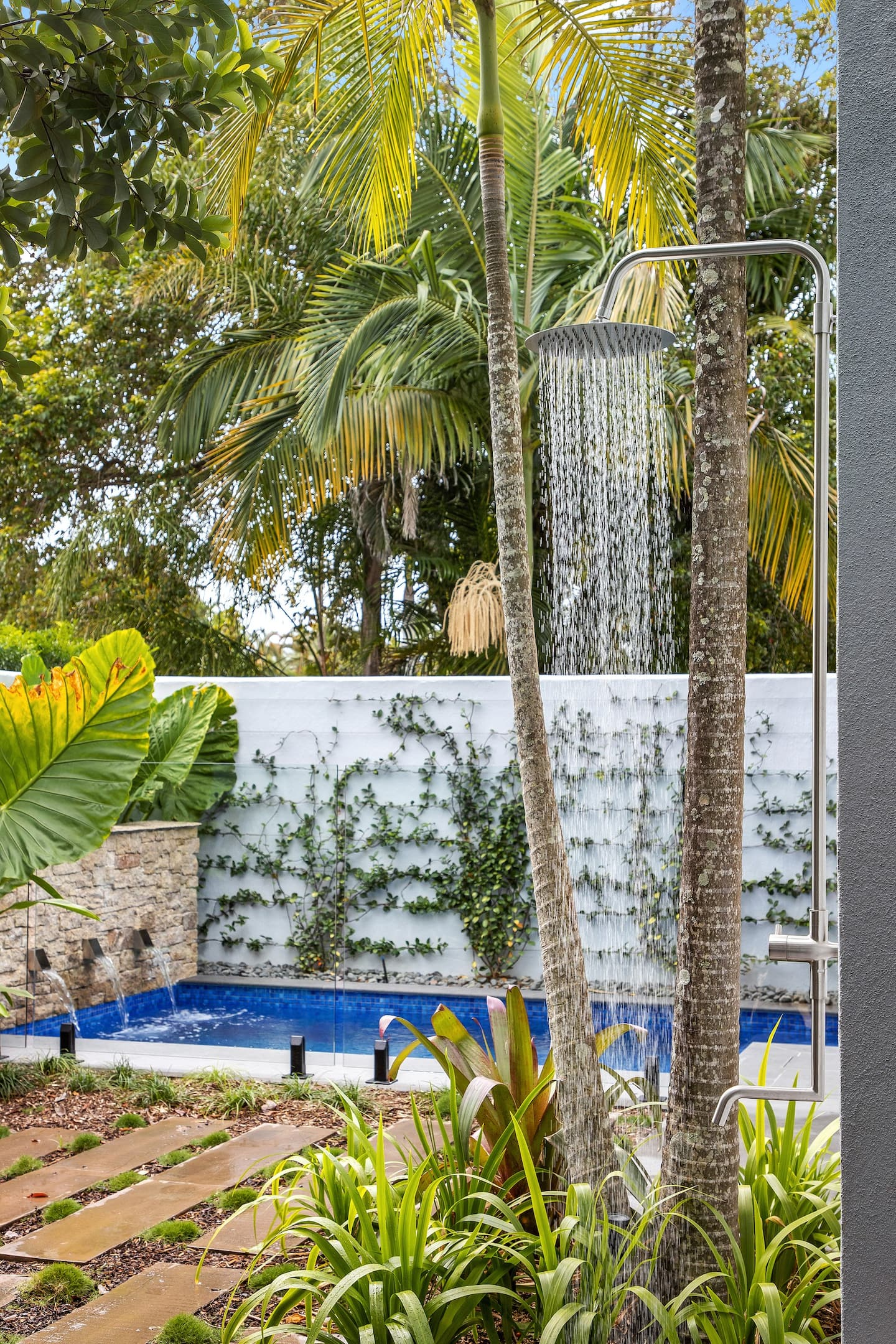 an outdoor shower with a pool in the background