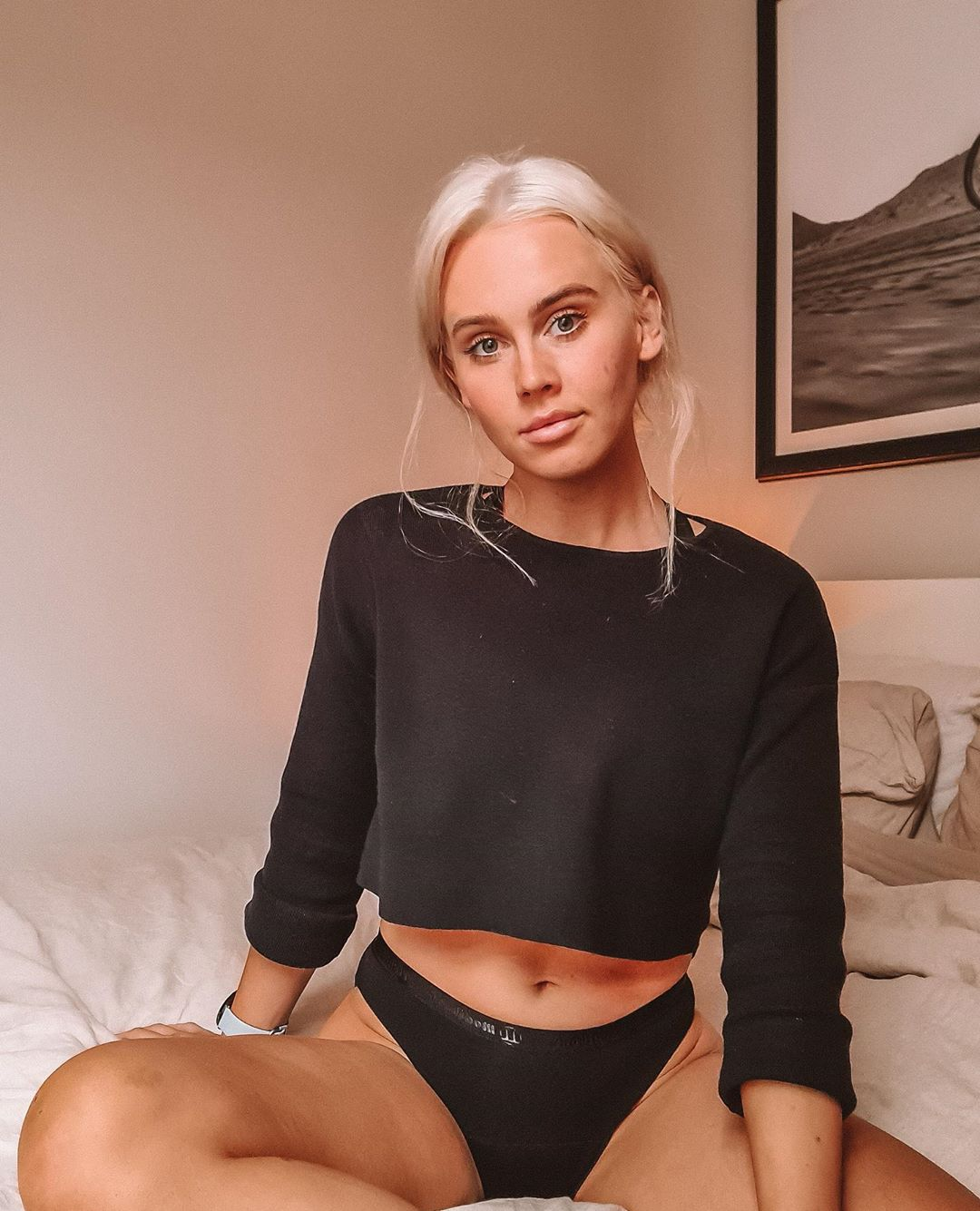 DJ Tigerlily Sits on her bed wearing a black cropped long sleeve top with black period-proof Modibodi underwear.
