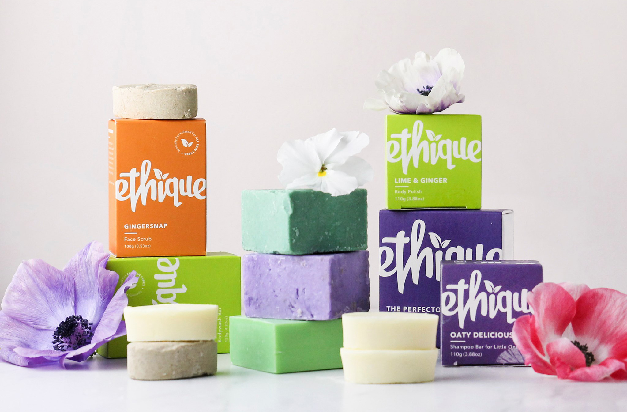 A collection of shampoo soap bars and brightly coloured boxes from Ethique