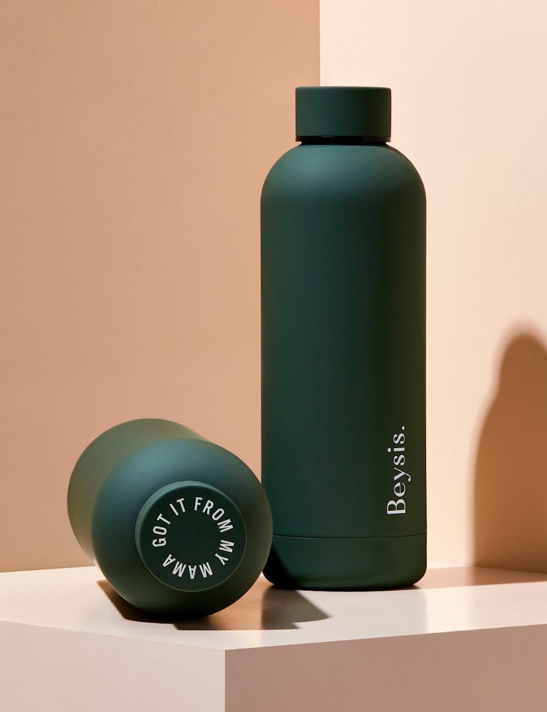 A sleek forest green water bottle stands on a peach shelf.