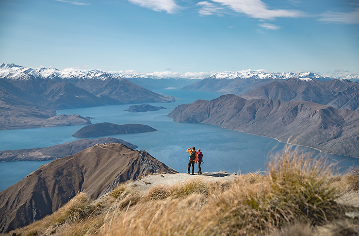 People stand atop Roys Peak Track looking at the amazing white capped mountains and scenery beyond.