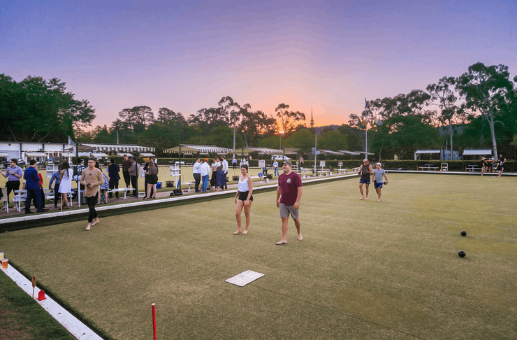 People playing barefoot bowls as the sun sets.