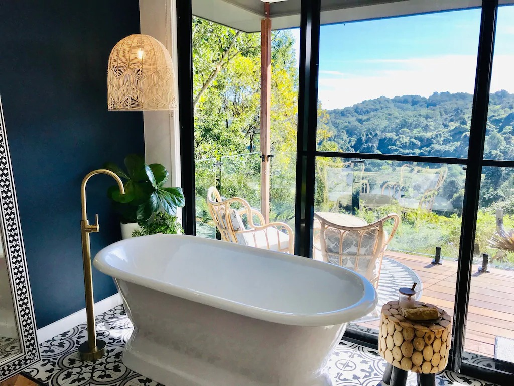 a bath by a floor to ceiling window overlook countryside