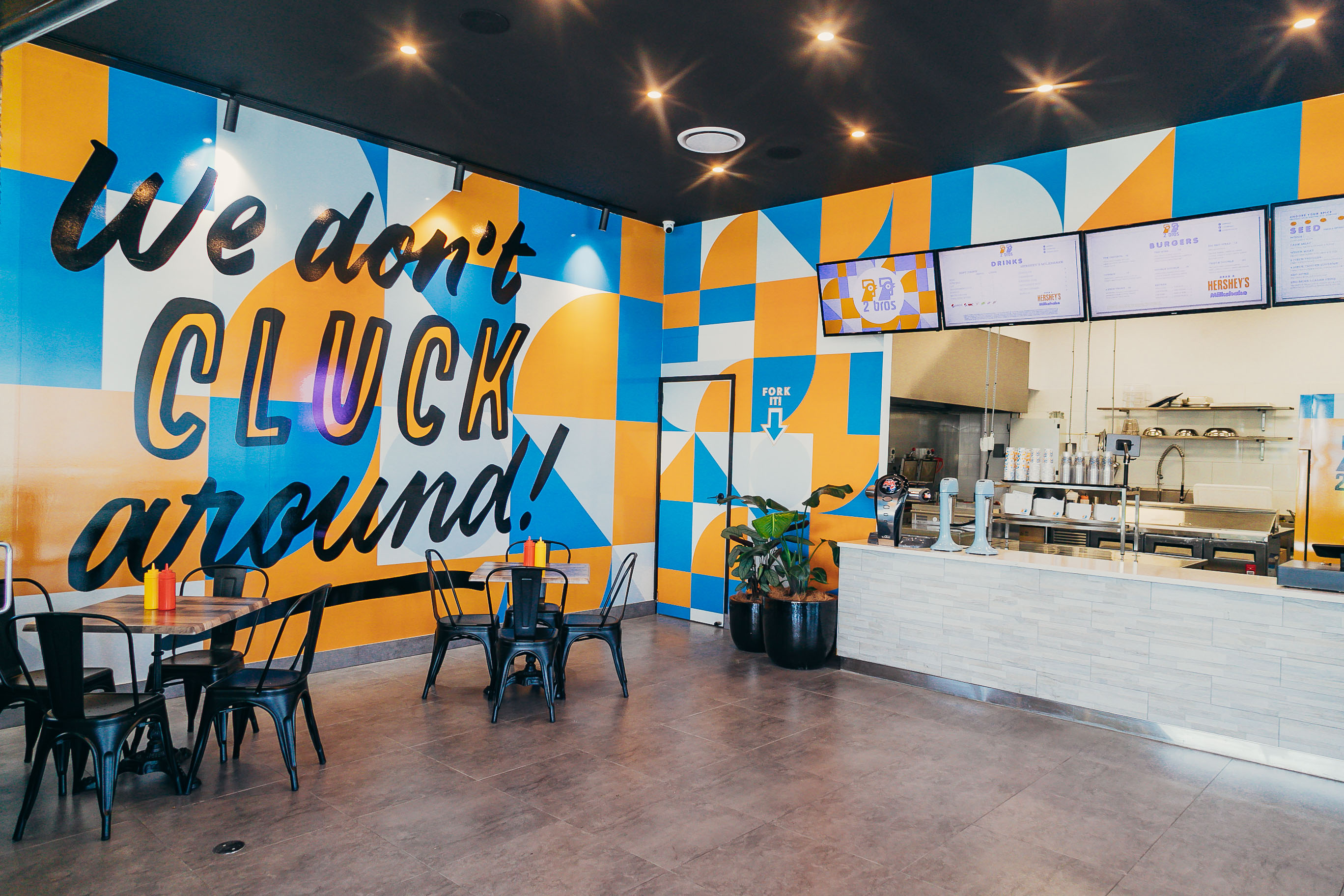 the interior of a fried chicken shop with yellow and blue accents