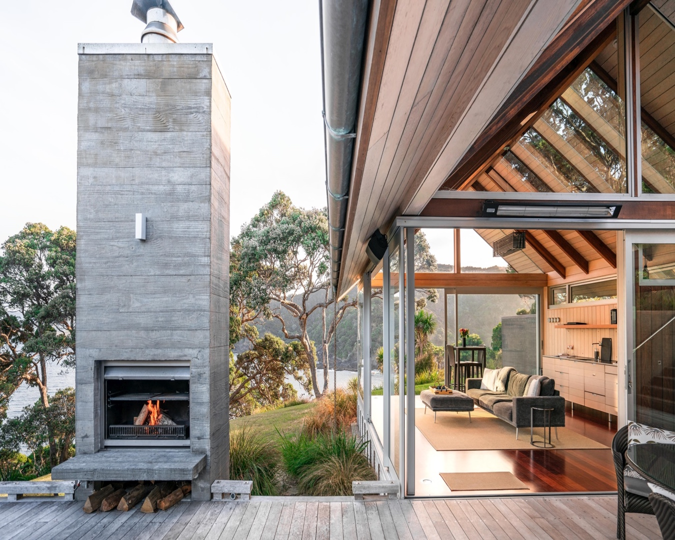 A stunning view of an outdoor fireplace and luxurious house made of glass overlooking the ocean.