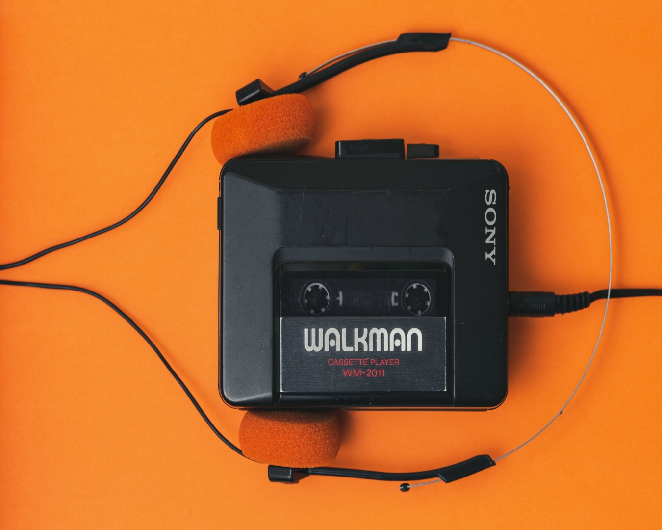 Old school cassette player with black and orange headphones on a bright orange background.