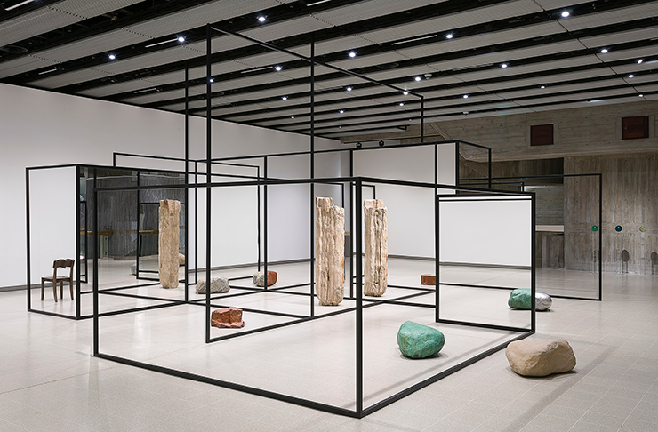 A black steel structure feels a white room within a brightly lit contemporary art gallery.