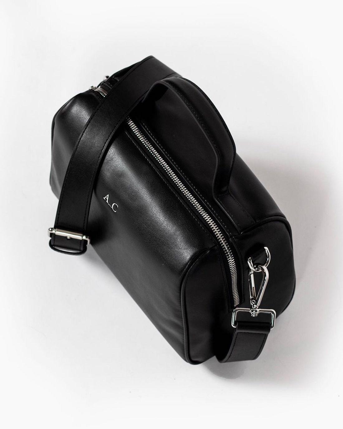 A black vegan leather handbag sits unopened.