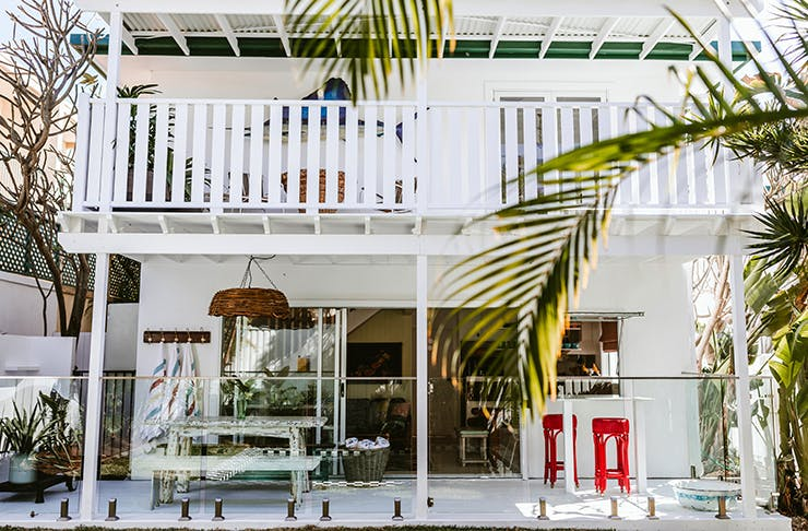 A two-storey white, beach-inspired home is surrounded by palms on the Gold Coast, Queensland.
