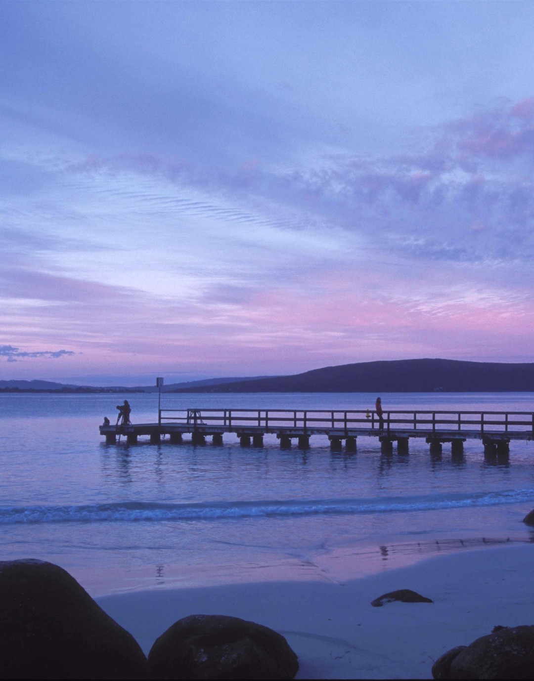 Two people stand on a wharf set to a purple and pink fairy floss sunset.